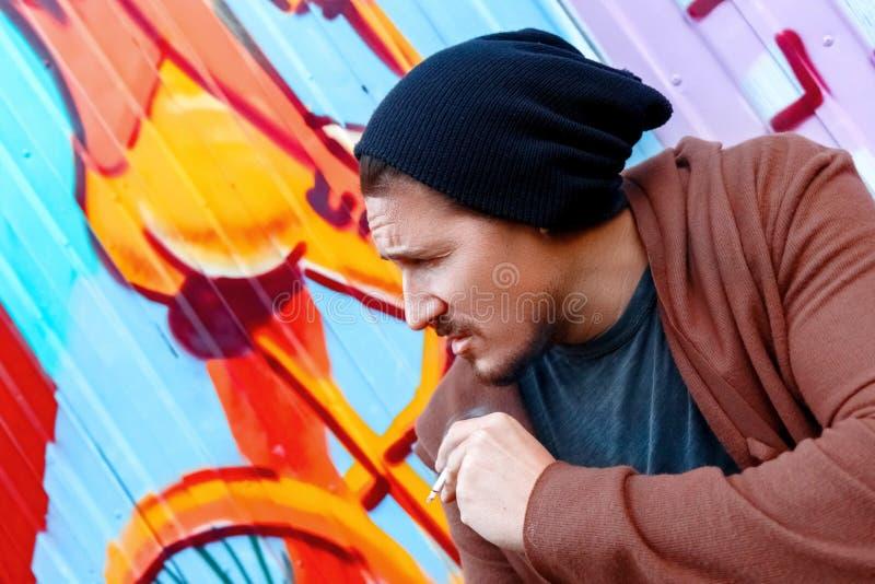 Brutal fuma cerca de la pared colorida en las calles de la ciudad grande fotografía de archivo libre de regalías