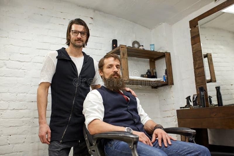 Brutal grabb i moderna Barber Shop Frisören gör frisyren en man med ett långt skägg Den ledar- fris?ren g?r frisyren royaltyfria bilder