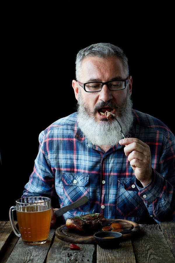 Brutal gray-haired adult man with a beard eats mustard steak and drinks beer, concept of a holiday, festival, Oktoberfest. Brutal gray haired adult man with a stock image