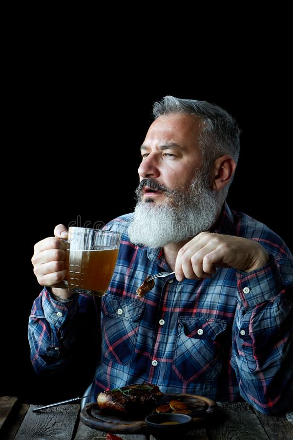 Brutal gray-haired adult man with a beard eats mustard steak and drinks beer, concept of a holiday, festival, Oktoberfest or St. Brutal gray haired adult man stock photo