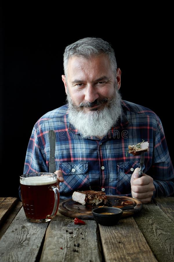 Brutal gray-haired adult man with a beard eats mustard steak and drinks beer, concept of a holiday, festival, Oktoberfest or St. Brutal gray haired adult man royalty free stock image