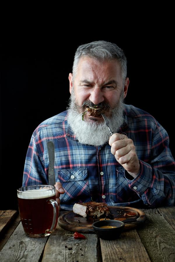 Brutal gray-haired adult man crazy about mustard steak and beer, concept of a holiday, festival, Oktoberfest or St. Patrick Day. Brutal gray haired adult man royalty free stock images