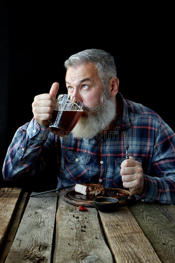 Brutal gray-haired adult man crazy about mustard steak and beer, concept of a holiday, festival, Oktoberfest or St. Patrick`s Day. Brutal gray haired adult man stock images