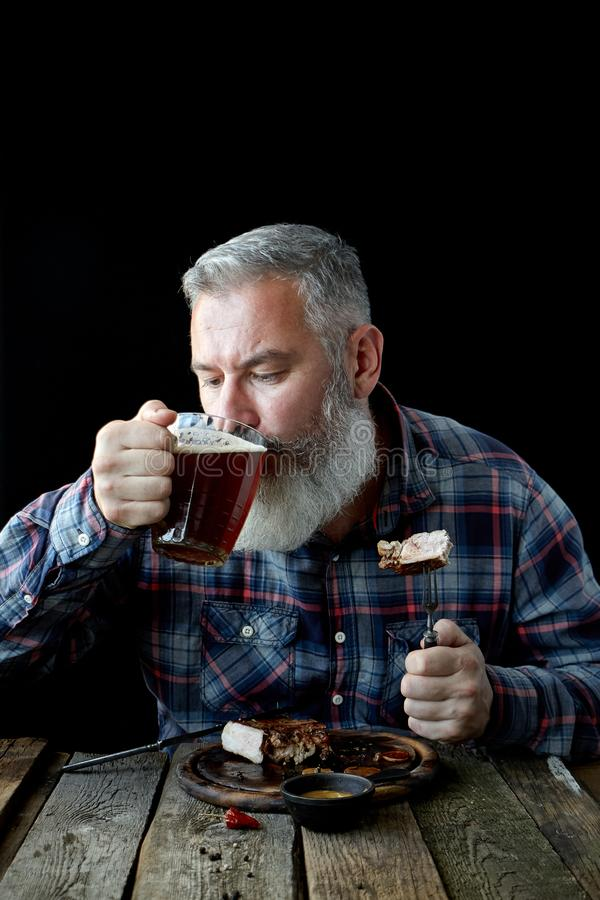 Brutal gray-haired adult man crazy about mustard steak and beer, concept of a holiday, festival, Oktoberfest or St. Patrick`s Day. Brutal gray haired adult man stock photo