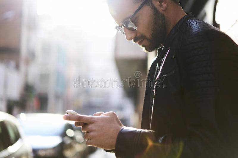 Brutal guy in a leather jacket and sunglasses royalty free stock image