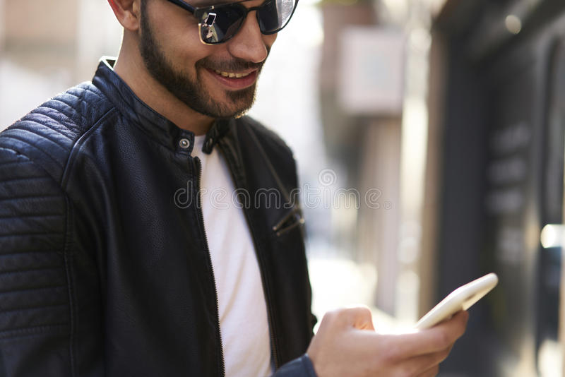 Brutal guy in a leather jacket and sunglasses royalty free stock photography