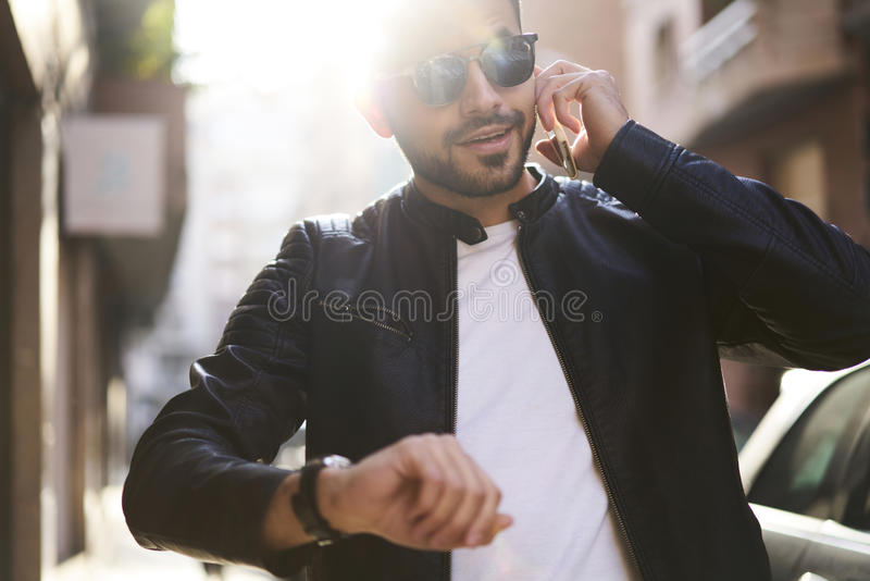 Brutal guy in a leather jacket and sunglasses stock image