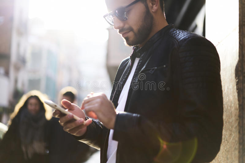 Brutal guy in a leather jacket and sunglasses royalty free stock images