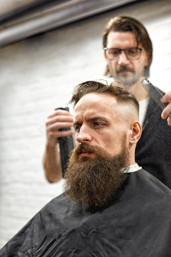 Brutal guy in modern Barber Shop. Hairdresser makes hairstyle a man with a long beard. Master hairdresser does hairstyle. Brutal guy in modern Barber Shop royalty free stock images