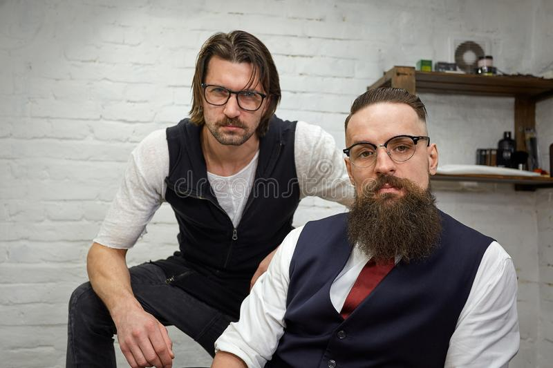 Brutal guy in modern Barber Shop. Hairdresser makes hairstyle a man with a long beard. Master hairdresser does hairstyle. Brutal guy in modern Barber Shop stock images