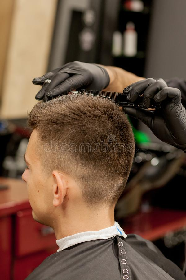Brutal guy in modern Barber Shop. Hairdresser makes hairstyle a man . Master hairdresser does hairstyle with hair clipper. Concept royalty free stock photography
