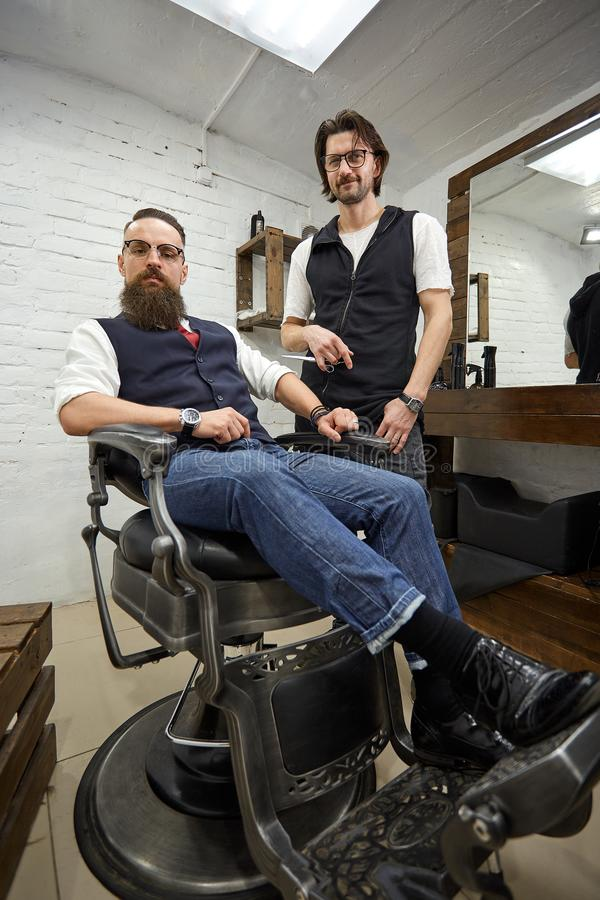 Brutal guy in modern Barber Shop. Hairdresser makes hairstyle a man with a long beard. Master hairdresser does hairstyle. Brutal guy in modern Barber Shop royalty free stock photography