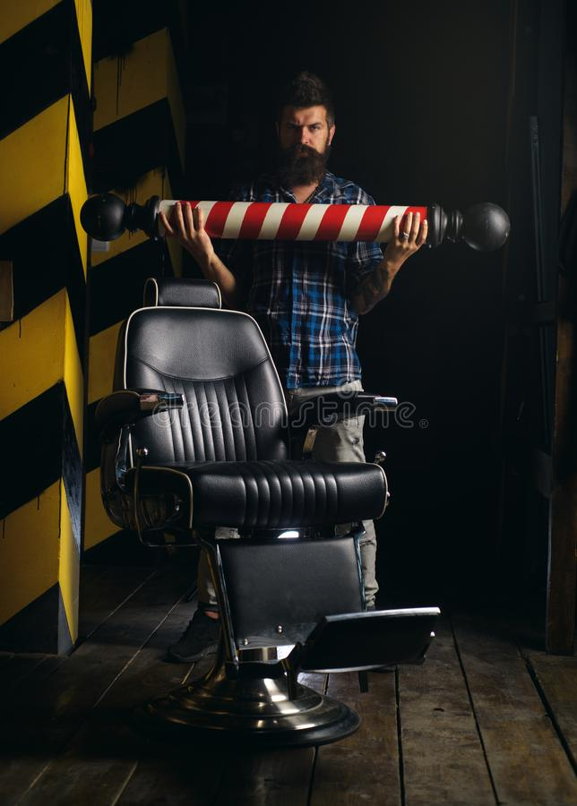 Brutal guy in modern Barber Shop. Razor blade. Bearded man getting haircut by hairdresser and sitting in chair at. Barbershop. He is doing styling with the stock photos