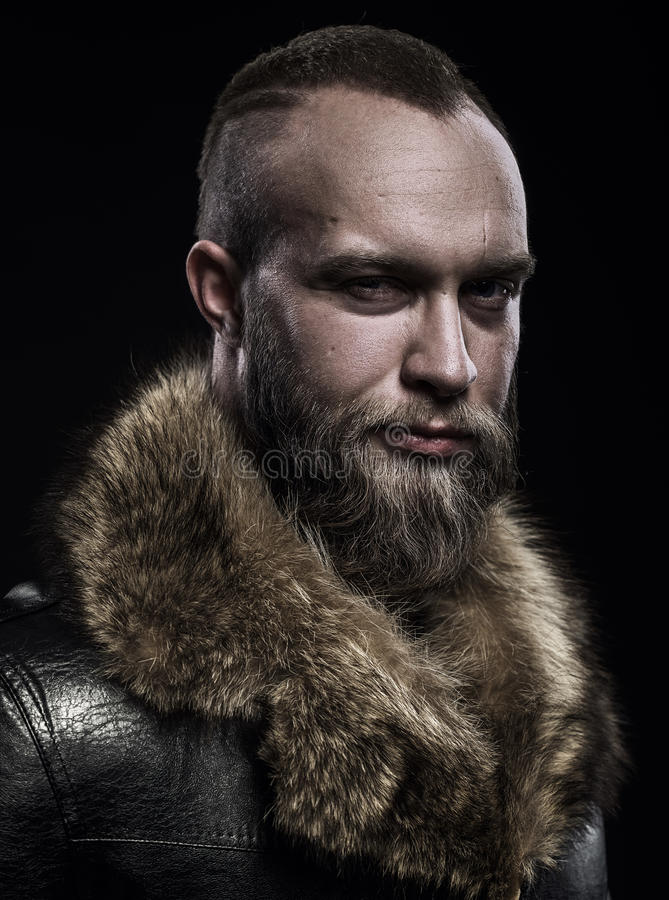 Brutal handsome glum unshaven man with long beard and moustache royalty free stock photos