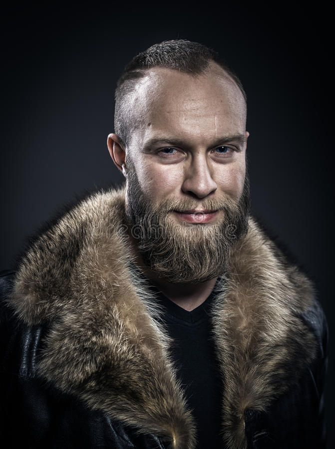 Brutal handsome smiling unshaven man with long beard and moustache in black fur coat with collar. royalty free stock photography