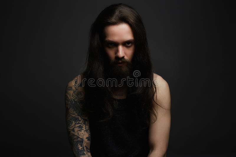 Brutal hipster boy with tattoo. Handsome bearded man.Brutal hipster boy with tattoo over dark background stock photos