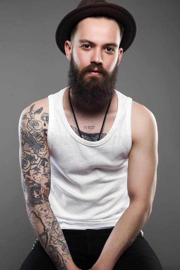 Brutal hipster boy with tattoo. Tattooed handsome Man in Hat. Brutal hipster boy with tattoo royalty free stock photo