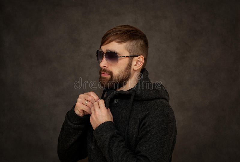 Brutal hipster guy in sunglasses, with a beard and fashionable hairstyle stock images