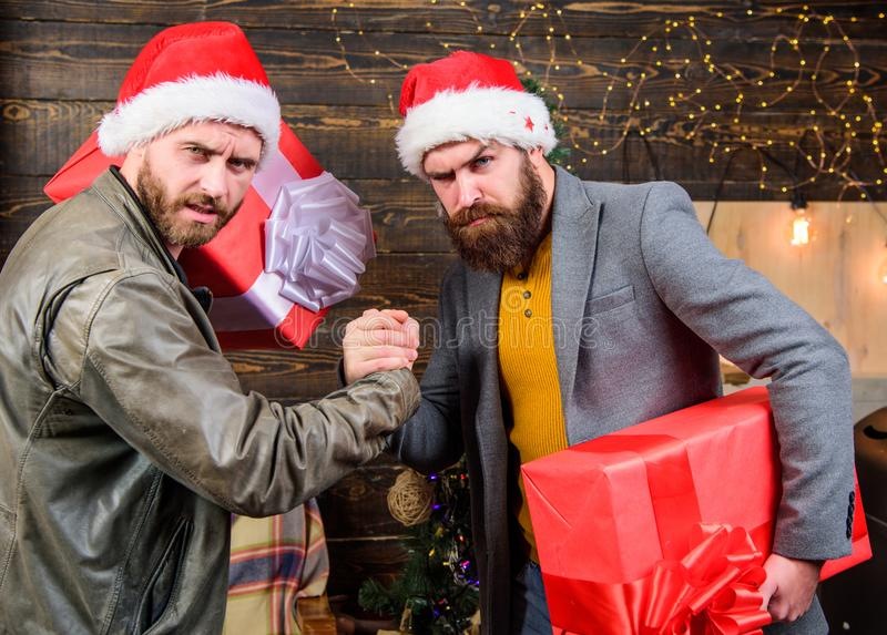 Brutal hipster guys celebrate christmas with gifts. Delivery christmas present. Christmas is coming. Get ready for. Christmas. Men wear santa hat hold gift royalty free stock photos