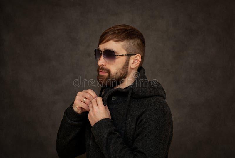 Brutal hipstergrabb i solglasögon, med en skägg- och innegrejfrisyr arkivbilder