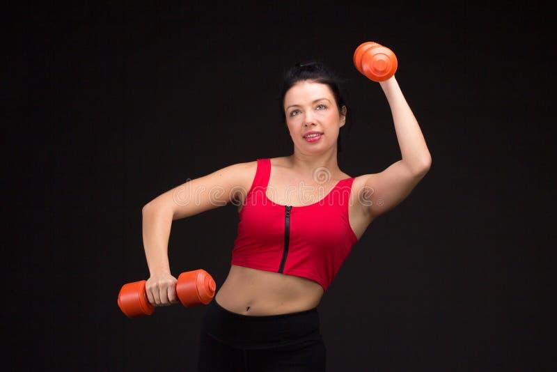 Brutal idrotts- kvinna som upp pumpar muscules med hantlar fotografering för bildbyråer