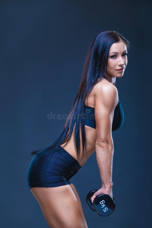 Brutal idrotts- sexig kvinna som upp pumpar muscules med hantlar Begreppet av övningssportar som annonserar en idrottshall arkivbild