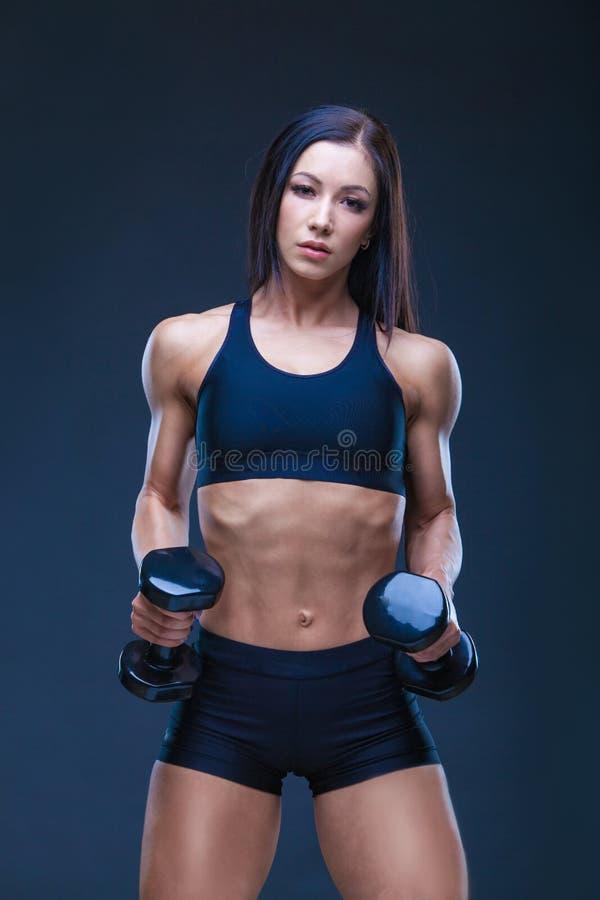 Brutal idrotts- sexig kvinna som upp pumpar muscules med hantlar Begreppet av övningssportar som annonserar en idrottshall arkivfoton