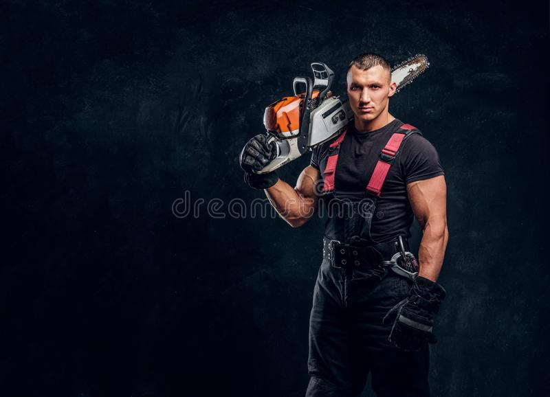Brutal logger posing with a chainsaw on his shoulder and looking at a camera with a confident look royalty free stock photos