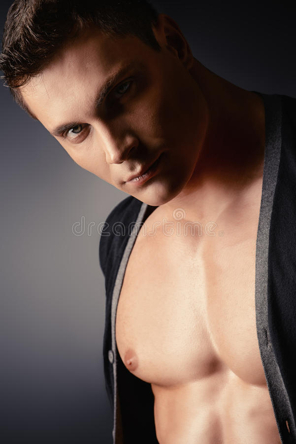 Brutal look. Portrait of a muscular young man posing over dark background stock photo