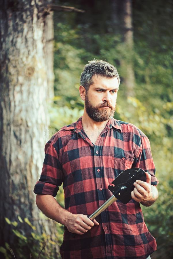 Brutal lumberjack with little spade wandering in wilderness. Ecologist with stylish beard exploring the woods. Young. Scientist working in nature, environment royalty free stock images