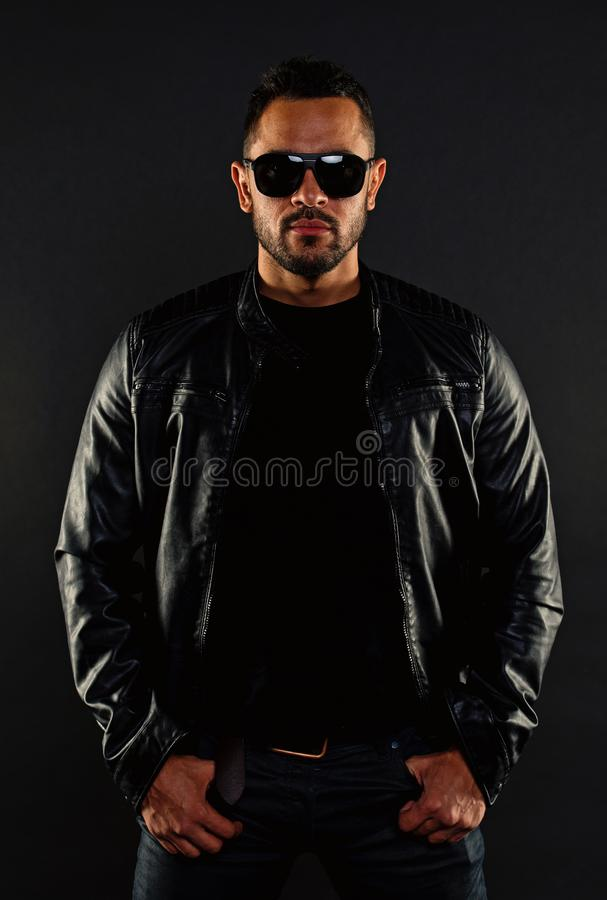 Brutal macho in leather jacket. Bearded man in fashion sunglasses. Mens sexuality and attraction. Fashion model in royalty free stock photography