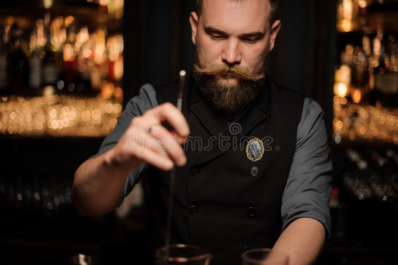 Bartender holds professional stirring spoon in bar. Brutal male bartender with beard and styled mustache holds professional long stirring spoon in bar stock image