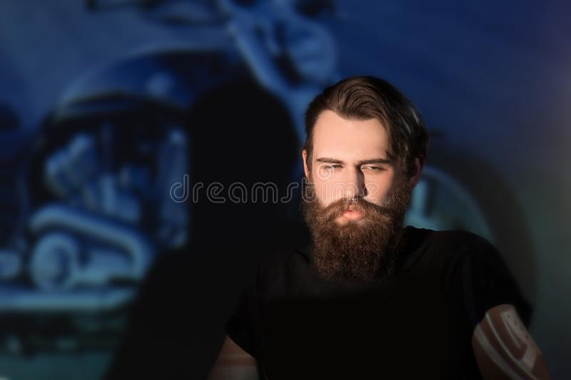 Brutal male biker looking through the slides of his motorcycle. royalty free stock photography