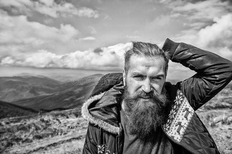 Brutal man, bearded hipster in winter jacket at mountain outdoor royalty free stock photos