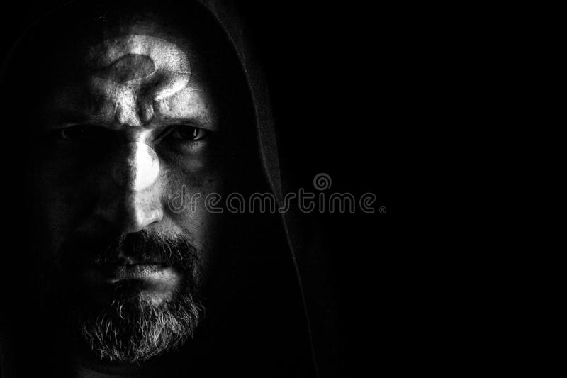 Brutal man with a gray beard in the hood with sharp shadows on a black background. Copy space. A brutal man with a gray beard, with the question on his face, in royalty free stock images