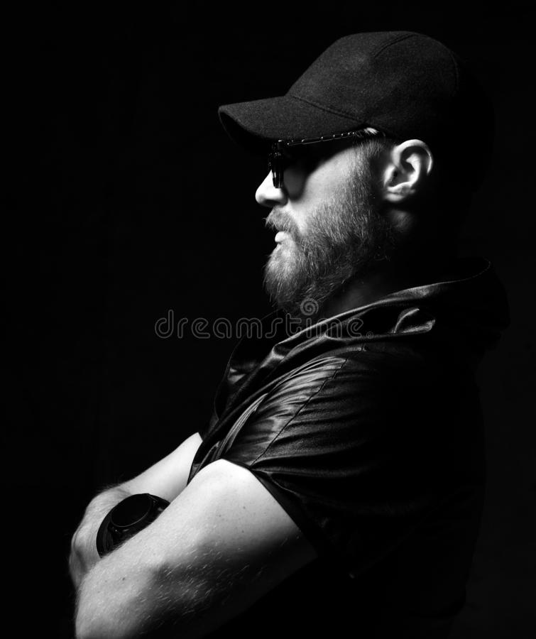 Brutal man in leather jacket, black cap and round sunglasses royalty free stock image