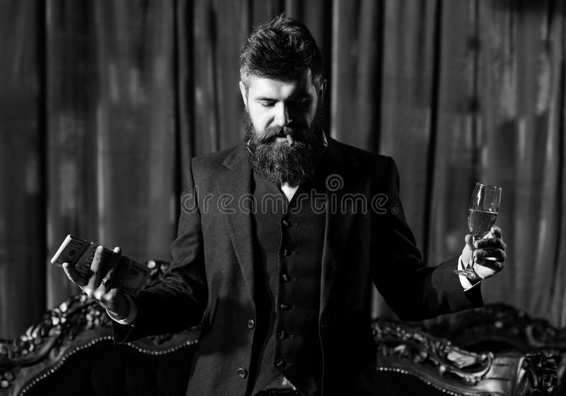 Brutal man with long beard has cigar, champagne and dollars. Millionaire in luxury suit smokes and holds money. royalty free stock image