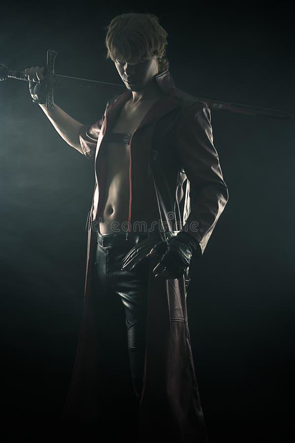 Brutal man med ett svärd som isoleras på svart fotografering för bildbyråer