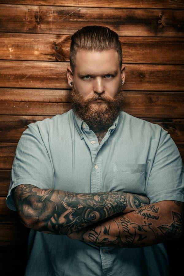 Brutal man med skägget och tatoos royaltyfri bild