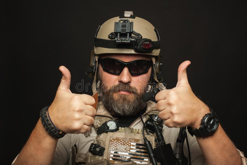 Brutal man in military desert uniform and body armor shows two fingers up on black background in Studio. The bearded player in the royalty free stock image