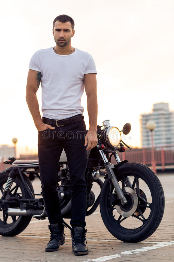 Brutal man near his cafe racer custom motorbike. Close up of a handsome rider guy in white blank t-shirt look to camera near classic style cafe racer motorcycle royalty free stock photography