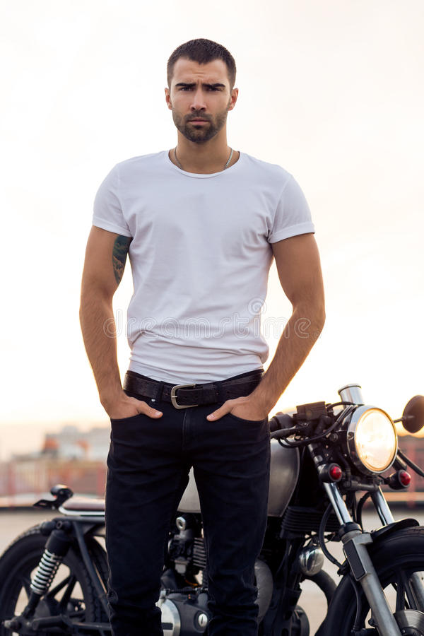 Brutal man near his cafe racer custom motorbike. Close up of a handsome rider man in white blank t-shirt look to camera near classic style cafe racer motorcycle stock photos
