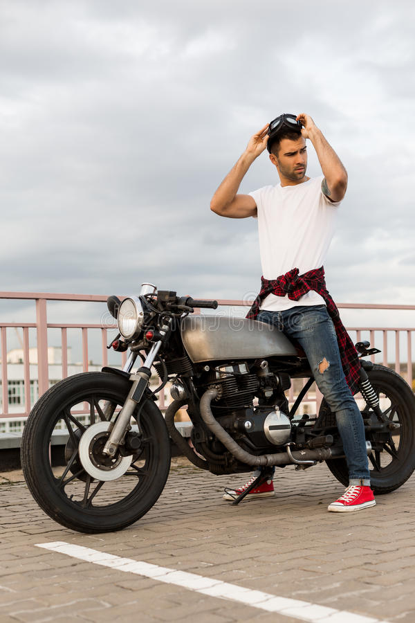 Brutal man near his cafe racer custom motorbike. Handsome rider man with beard and mustache put on protection glasses and ready to go on classic style biker stock photo