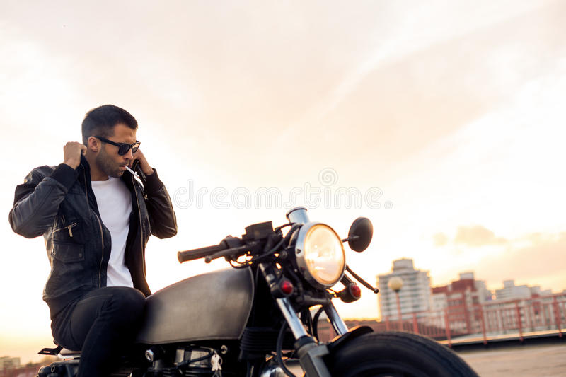 Brutal man sit on cafe racer custom motorbike. Handsome rider guy with beard and mustache smoking cigaret and correct biker jacket sit on classic style cafe stock images