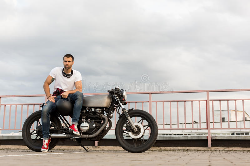 Brutal man sit on cafe racer custom motorbike. Rider man with beard and mustache in red sneakers and black googles sit on classic style biker cafe racer stock images
