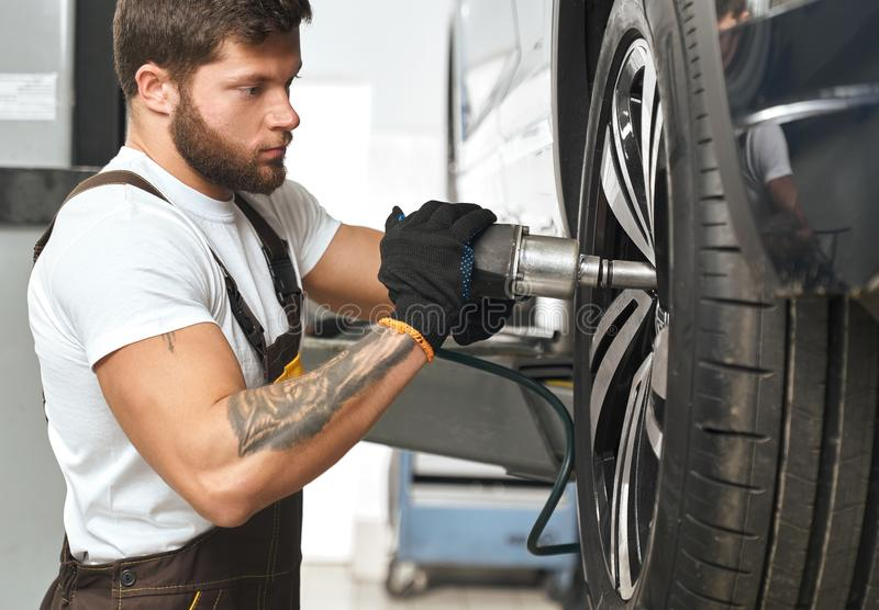 Brutal mechanic fixing hubcap of car wheel. Bearded, brutal mechanic fixing hubcap of auto wheel, using equipment. Muscular man in white t shirt with tattoo on stock photography