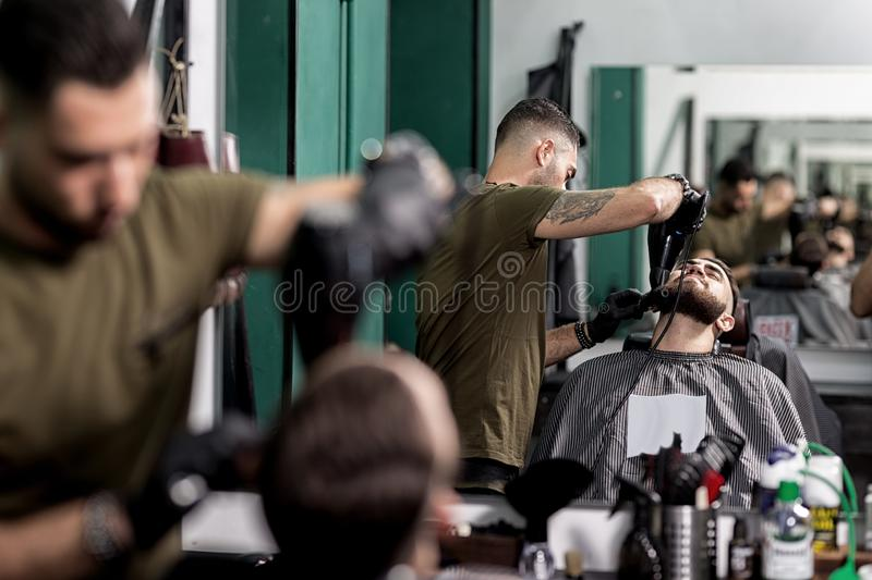 Brutal man with a beard sits in front of the mirror at a barbershop. Barber trims mens beard with scissors stock photo
