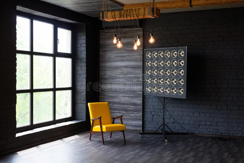 Brutal modern interior in a dark color with a yellow leather chair and big window. Loft style living room royalty free stock photography