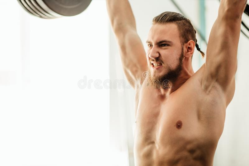 Brutal muscular man with beard train with barbell raised over head in gym stock image