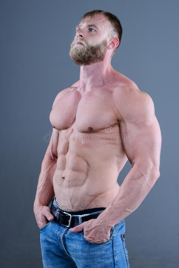 Brutal muscular man in studio on gray background fitness model stock photos